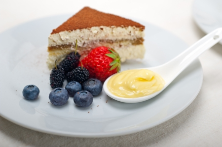 classic Italian tiramisu dessert with berries and custartd pastry cream on side  photo