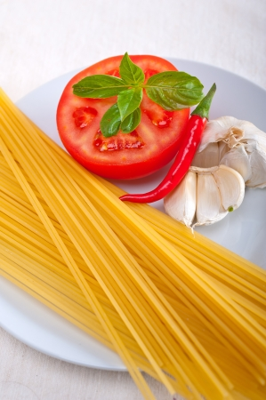 Italian spaghetti pasta tomato raw  ingredients basil garlic and red chili pepper Stock Photo - 19277484
