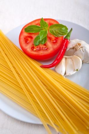 Italian spaghetti pasta tomato raw  ingredients basil garlic and red chili pepper Stock Photo - 19277484