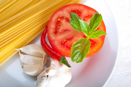 Italian spaghetti pasta tomato raw  ingredients basil garlic and red chili pepper Stock Photo - 19277479