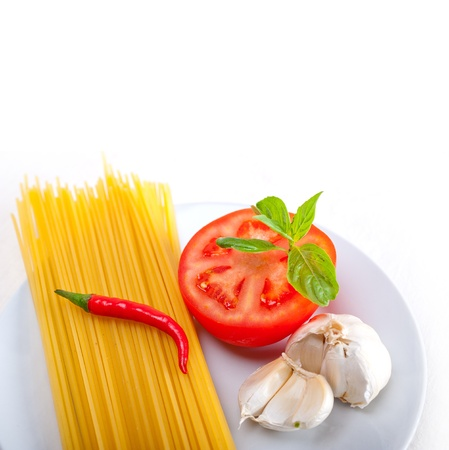 Italian spaghetti pasta tomato raw  ingredients basil garlic and red chili pepper photo