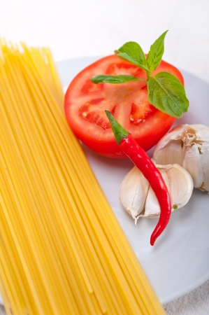 Italian spaghetti pasta tomato raw  ingredients basil garlic and red chili pepper Stock Photo - 19277481
