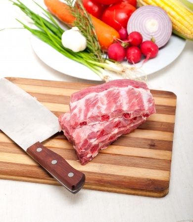 chopping fresh pork ribs with vegetables and herbs ready to cook photo