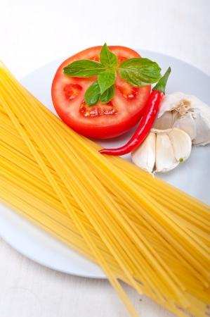 Italian spaghetti pasta tomato raw  ingredients basil garlic and red chili pepper Stock Photo - 19277547