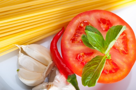 Italian spaghetti pasta tomato raw  ingredients basil garlic and red chili pepper Stock Photo - 19277550