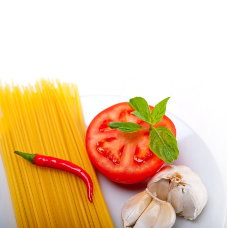 Italian spaghetti pasta tomato raw  ingredients basil garlic and red chili pepper Stock Photo - 19277555