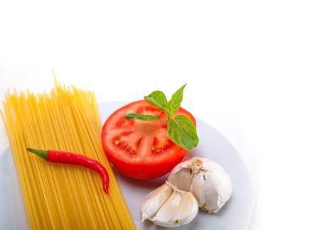 Italian spaghetti pasta tomato raw  ingredients basil garlic and red chili pepper Stock Photo - 19277543