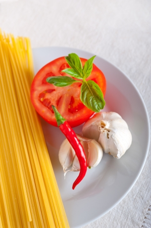 Italian spaghetti pasta tomato raw  ingredients basil garlic and red chili pepper Stock Photo - 19277549