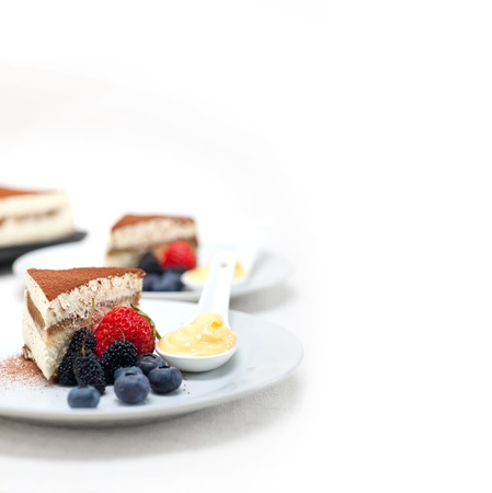 classic Italian tiramisu dessert with berries and custartd pastry cream on side  photo
