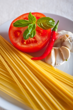 Italian spaghetti pasta tomato raw  ingredients basil garlic and red chili pepper Stock Photo - 19413078