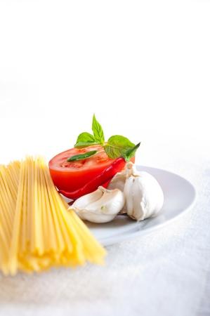 Italian spaghetti pasta tomato raw  ingredients basil garlic and red chili pepper Stock Photo - 19413084
