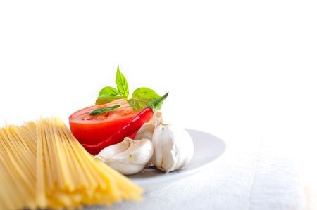 Italian spaghetti pasta tomato raw  ingredients basil garlic and red chili pepper Stock Photo - 19413065