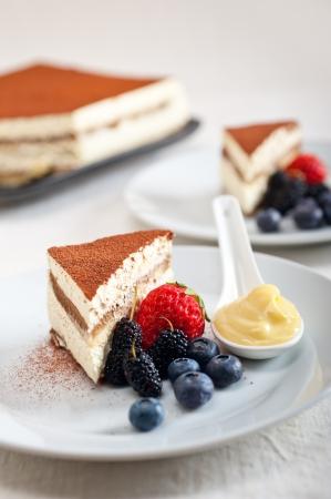 tiramisu: classic Italian tiramisu dessert with berries and custartd pastry cream on side