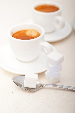 Italian espresso coffee fresh brewed macro closeup with sugar cubes photo