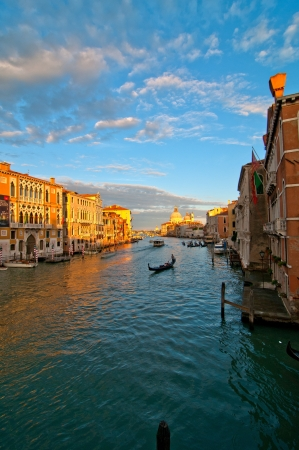 Venice Italy grand canal view from the top of Accademia bridge with 'Madonna della Salute' church on background at sunset photo