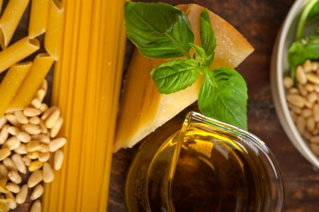 Italian basil pesto ingredients and raw pasta over old wood macro photo