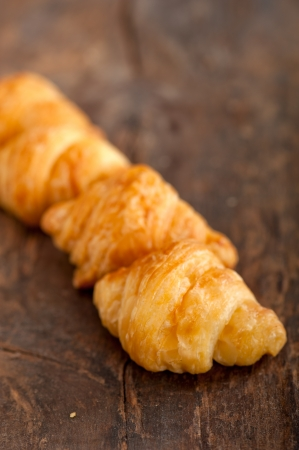 buttered: fresh croissant french brioche over old wood table
