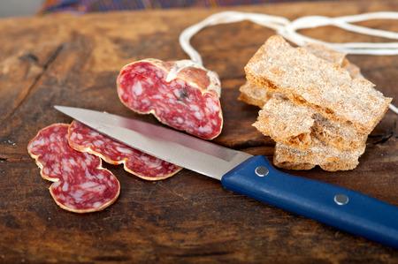 salame: slicing italian salame pressato pressed over old wood table