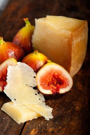 italian pecorino cheese and fresh figs macro closeup over old wood boards photo