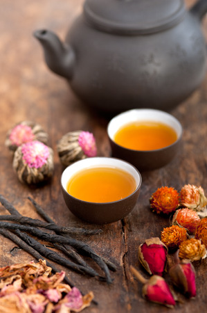raw tea: Chinese style herbal floral tea over wood table with raw ingredients