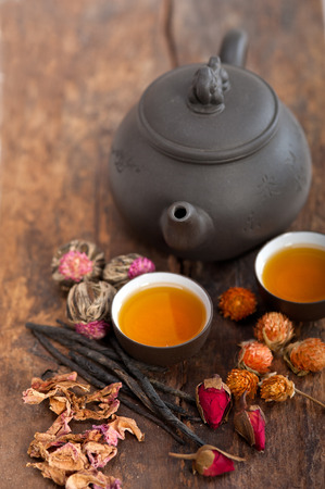Chinese style herbal floral tea over wood table with raw ingredients photo