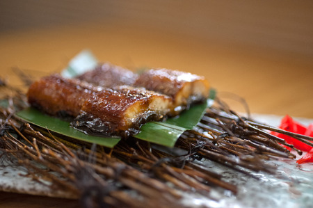 Japanese style roasted eel served on palm leaf photo