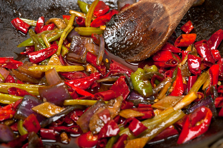fried chili pepper and vegetable on a iron wok pan photo