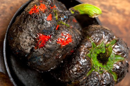 scorched: three fresh bell peppers charcol scorched  over old wood table on a skillett