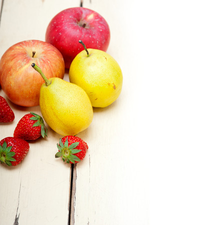 fresh fruits apples pears and strawberry on a white wood table photo