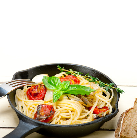 cast iron red: italian spaghetti pasta with baked tomatoes  basil and thyme sauce on a cast iron skillet