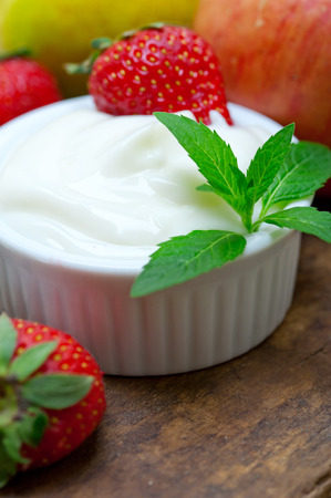 fresh fruits and whole milk yogurt on a rustic wood table photo