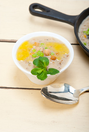Hearty Middle Eastern Chickpea and Barley Soup with mint leaves on top photo