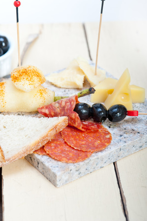cold cut: cold cut assortment cheese salami and fresh pears served on a granite stone Stock Photo