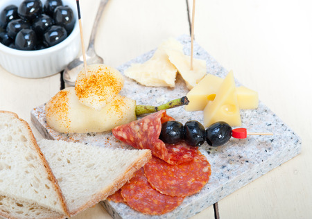 stone cold: cold cut assortment cheese salami and fresh pears served on a granite stone Stock Photo