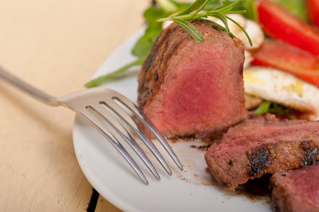 side of beef: beef filet mignon grilled with fresh vegetables on side ,mushrooms tomato and arugula salad Stock Photo