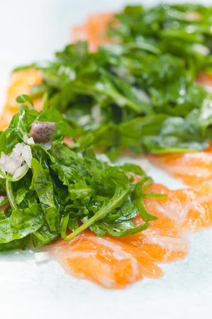 caper: Fresh salmon carpaccio sushi sashimi with arugula rocket salad and caper on top