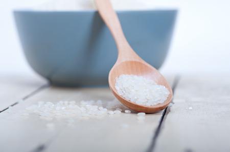 arroces: arroz blanco crudo en una cuchara de madera y un recipiente azul extrema de cerca Foto de archivo