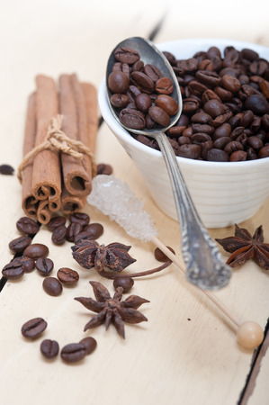comida arabe: coffe sugar and spice on silver spoon over white wood rustic table