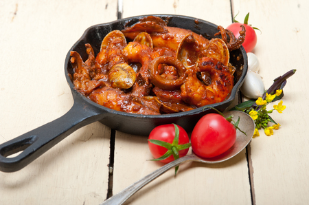ove: fresh seafood stew prepared on an iron skillet ove white rustic wood table