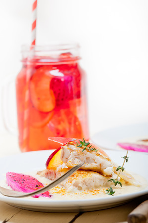 sea bream: sea bream orata  fillet butter pan fried with fresh peach prune and dragonfruit slices thyme on top Stock Photo