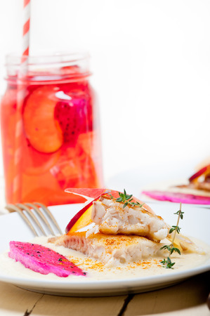 dragonfruit: sea bream orata  fillet butter pan fried with fresh peach prune and dragonfruit slices thyme on top Stock Photo