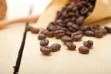 cuerno de la abundancia: los granos de café espresso en una cornucopia cono de papel sobre el fondo blanco