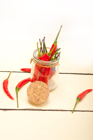 red chili peppers on a glass jar over white wood rustic table Stock Photo