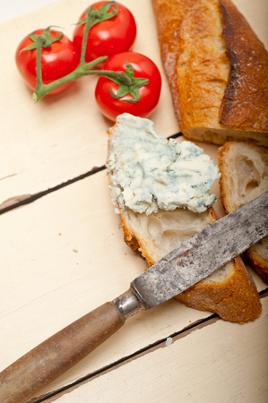 fresh blue cheese spread ove french baguette with cherry tomatoes on side Stock Photo