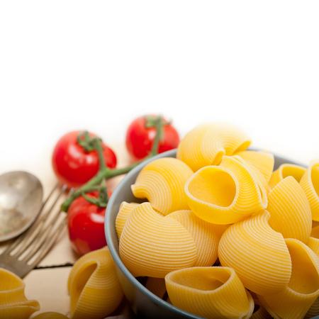 maccheroni: Italian snail lumaconi pasta with ripe cherry tomatoes sauce ingredients Stock Photo