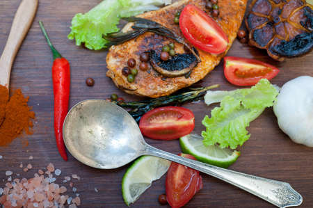 wood fired hoven cooked chicken on wood board with herbs spices and vegetables Archivio Fotografico