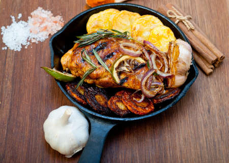 roasted grilled BBQ chicken breast with herbs and spices rustic style on iron skillet