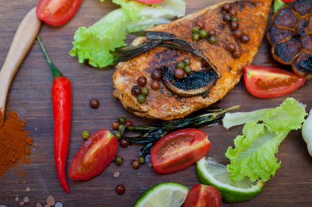 wood fired hoven cooked chicken breast on wood board with herbs spices and vegetables