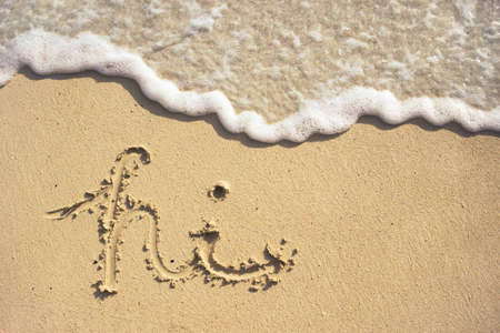 Hi written in the sand on a nice beach in Hawaii with the waves coming up. 版權商用圖片