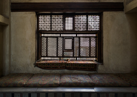 interleaved: Aged interleaved wooden window Mashrabiya and a built-in couch in a room of a historic house, Cairo, Egypt